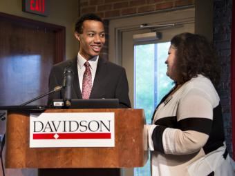 Student stands at podium with Kristin Booher to accept prize