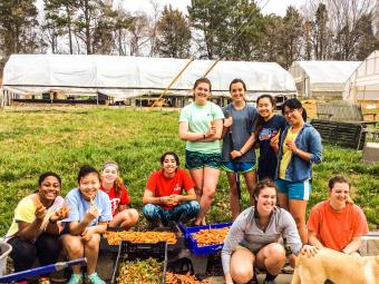 Farm volunteer students pose with vegetables they helped harvest