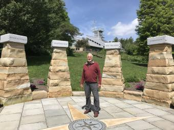John Huie '60 stands inside stone monument