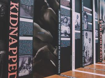 EJI Museum Exhbit with black and white photos of enslaved persons, the word Kidnapped at the front