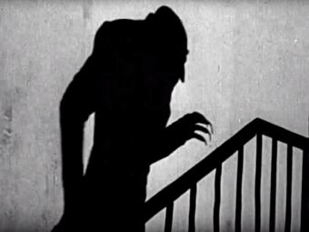 Halloween video screen shot of creepy shadow up the stairs