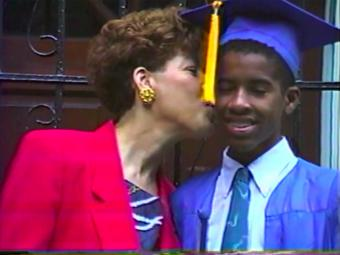 Family member kisses son on cheek, screenshot of documentary