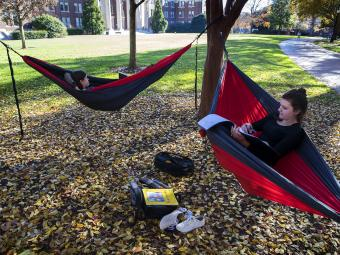 Two students in hammocks on the lawn