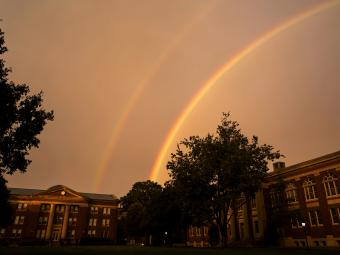 Sky rainbow over college buildings and trees
