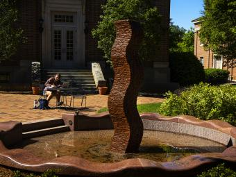 Student studying by art sculpture