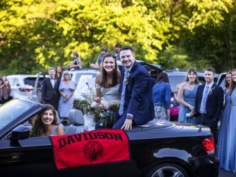 Caroline Bell '17 in car with husband and Davidson flag hanging out
