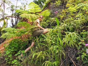 Lydia climbs hillside with vegetation and magenta orchids