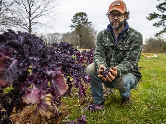 Joe Rowland kneels with Produce at Davidson College Farm